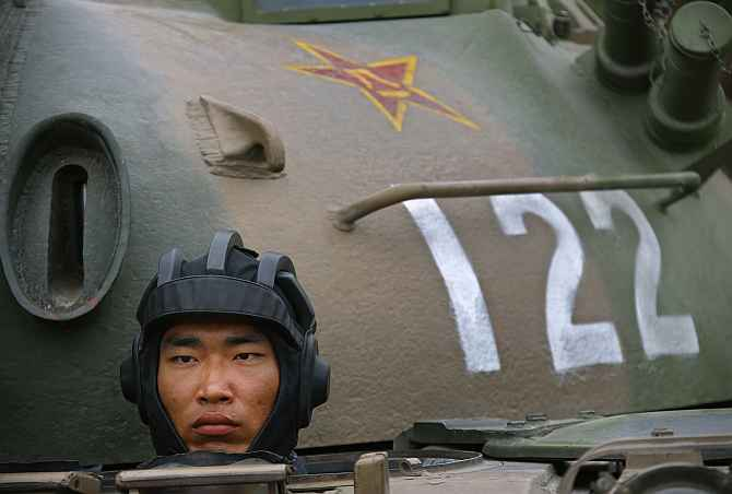 A Chinese soldier stands inside a tank during a military exercise in Beijing.