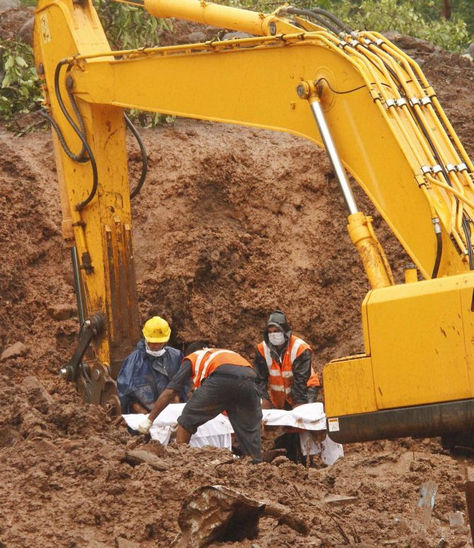 NDRF personnel recover a body from the debris at landslide-hit Malin village in Pune, Maharashtra