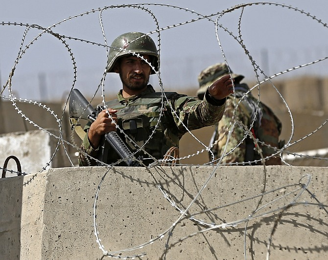 An Afghan National Army soldier keeps watch at the gate of a British-run military training academy Camp Qargha, in Kabul August 5