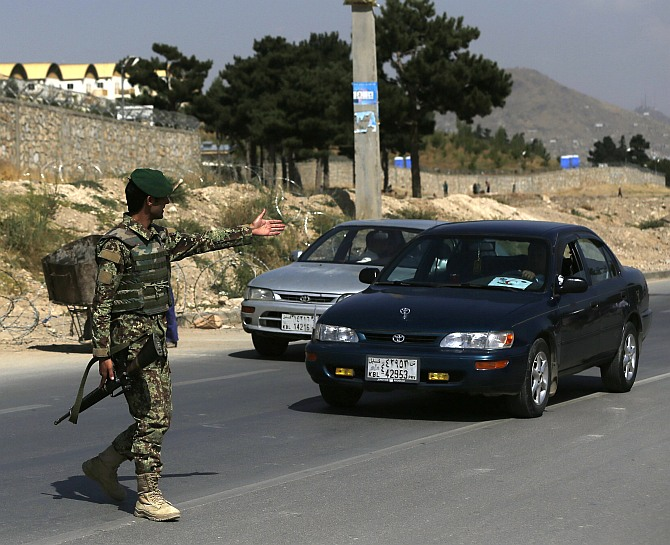 An Afghan National Army soldier gestures at a car at the gate of a British-run military training academy Camp Qargha, in Kabul