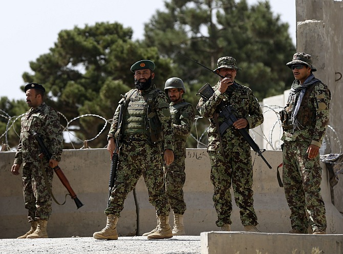 Afghan National Army soldiers keep watch at the gate of a British-run military training academy Camp Qargha, in Kabul August 5