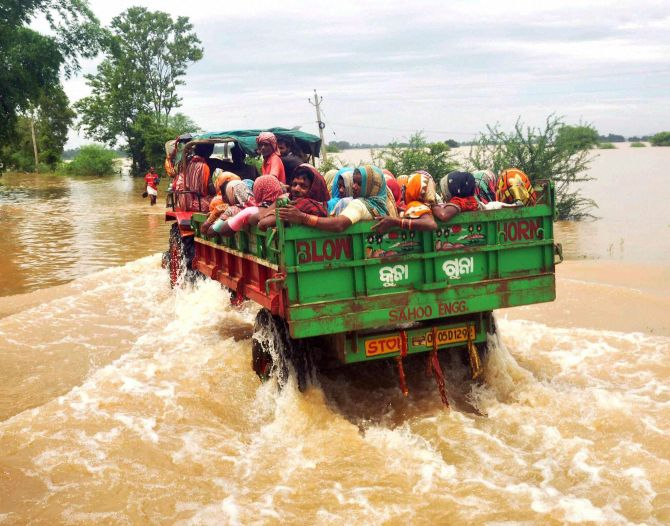People shift by a tractor from a flooded village in Khurda district of Odisha on Tuesday