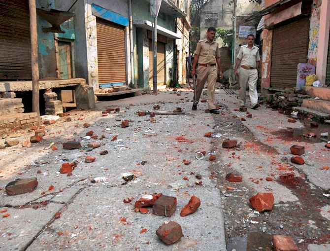 Policemen walk on a road littered with bricks and stones thrown during a communal clash in Muzaffarnagar.