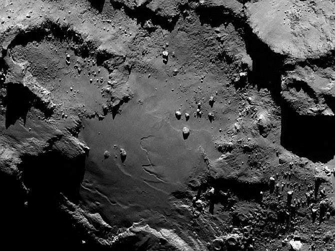 Stunning close up detail focusing on a smooth region on the 'base' of the 'body' section of comet 67P/Churyumov-Gerasimenko. The image was taken by Rosetta's OSIRIS narrow-angle camera and downloaded on August 6. The image clearly shows a range of features, including boulders, craters and steep cliffs. The image was taken from a distance of 130 km and the image resolution is 2.4 metres per pixel.