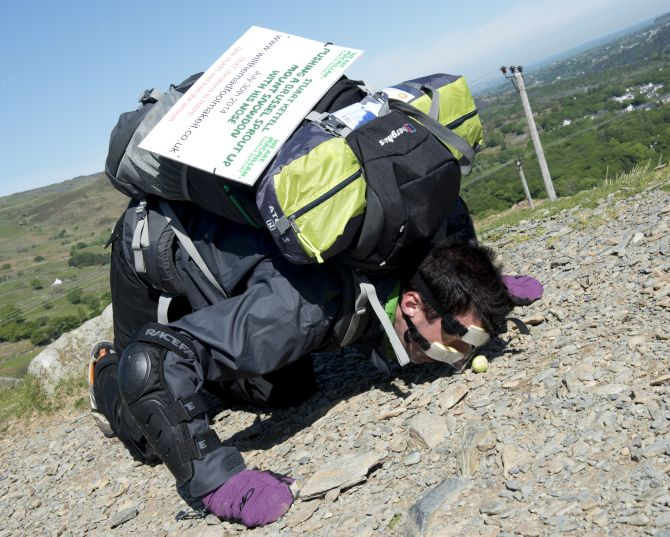 Man rolls brussel sprouts to the top of mountain with his nose