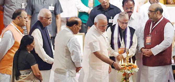Prime Minister Narendra Modi lights a lamp as BJP President Amit Shah and senior leaders LK Advani, M M Joshi, Rajnath Singh, M Venkaiah Naidu, Arun Jaitley and Gujarat CM Anandiben Patel look on during the partys national council meet