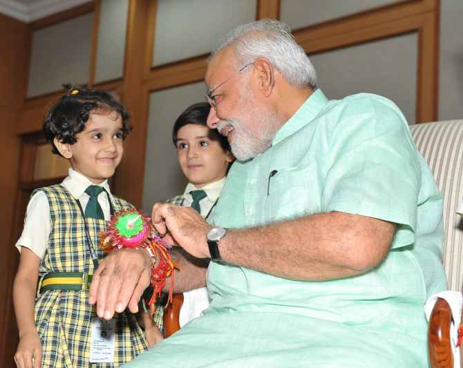 Children tying Rakhi onto the wrist of Prime Minister Narendra Modi in New Delhi on Sunday