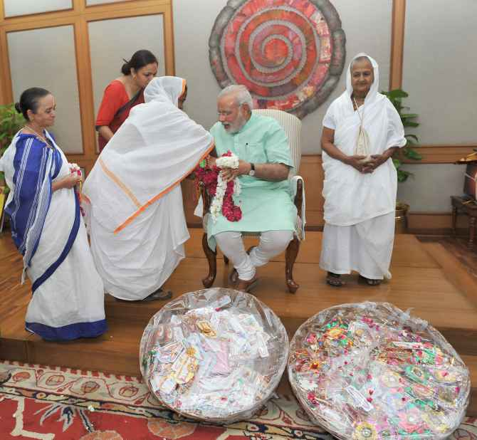 Widows from Vrindavan and Varanasi tying 'Rakhi' onto the wrist of Prime Minister Narendra Modi on Sunday