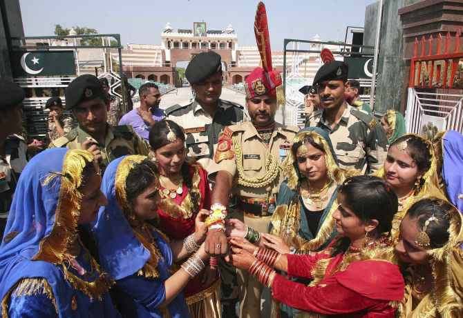 Women tie Rakhis onto the wrist of a BSF soldier during the Raksha Bandhan celebrations at the India-Pakistan joint check post at the Wagah border on Sunday