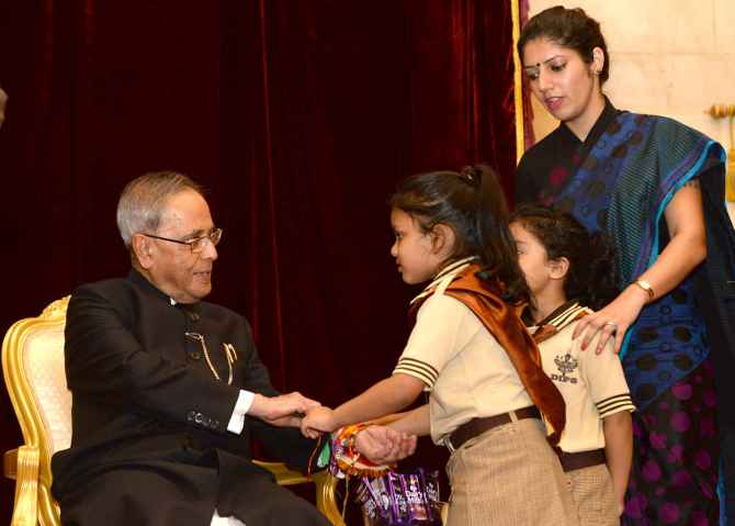 Children tying 'Rakhi' onto the wrist of President Pranab Mukherjee on the occasion of 'Raksha Bandhan', in New Delhi on Sunday.