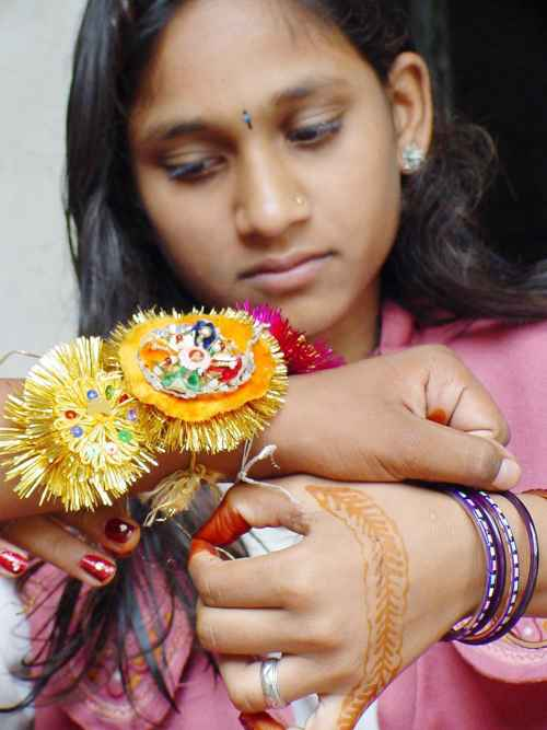 A little girl ties Rakhi onto the wrist of her brother in Bhopal