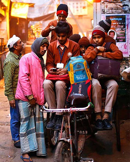 A school boy shows his mobile phone to a rickshaw puller who takes him and other students to school on a cold winter morning in old Delhi.