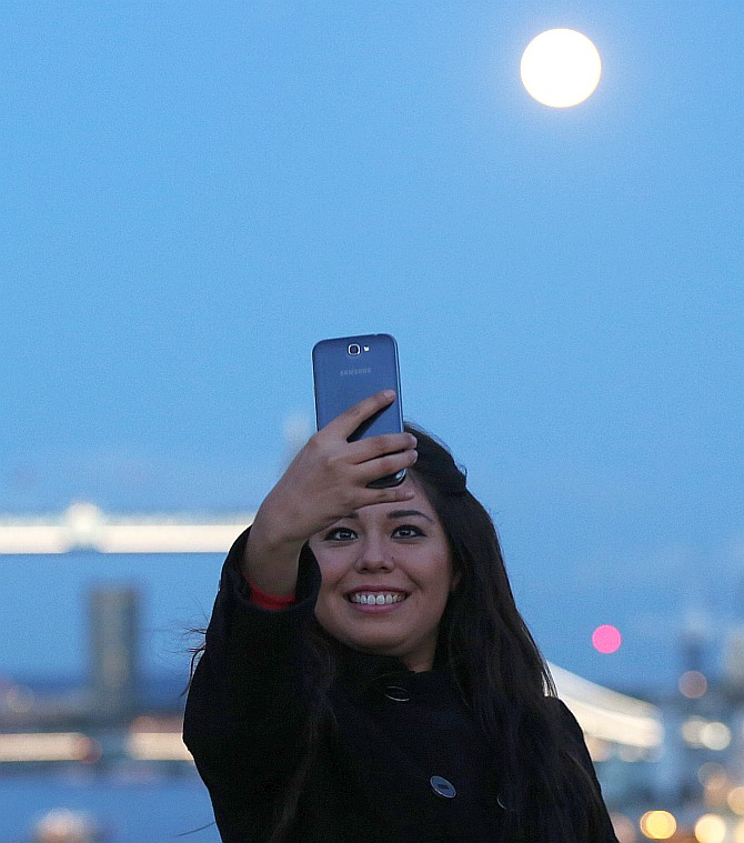 A woman takes a selfie as the supermoon rises over Tower Bridge in London