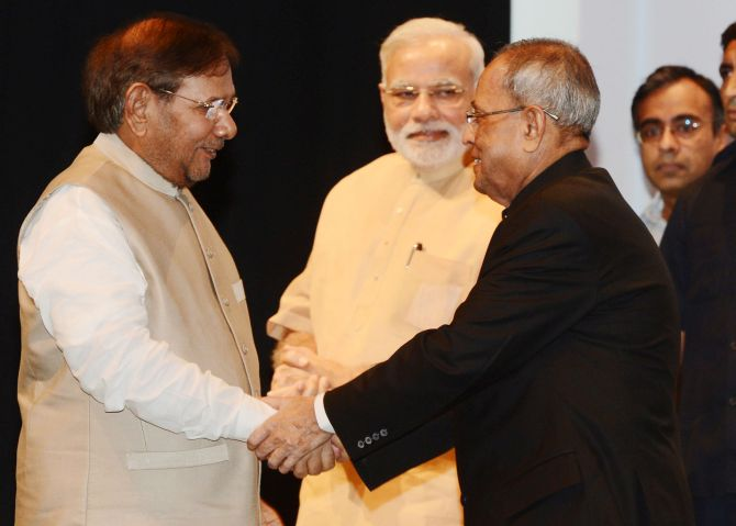 Sharad Yadav shakes hands with President Mukherjee after being awarded best parliamentarian.
