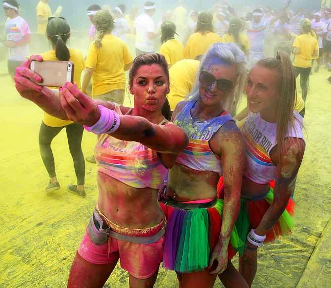 Participants pose for a selfie as they take part in the Colour Run in London.