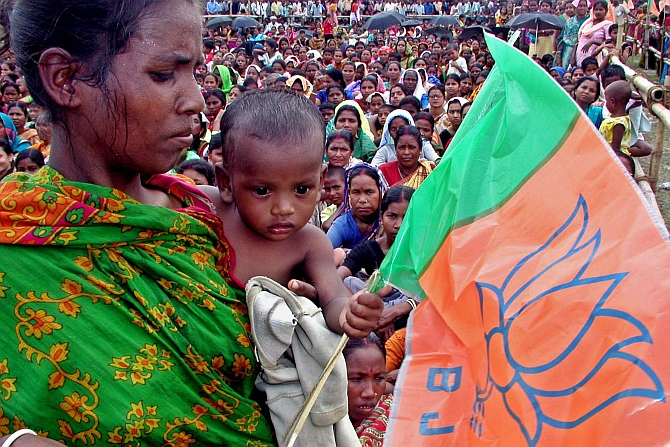 An woman holds her child and flag of ruling Bharatiya Janata Party  during an election campaign rally