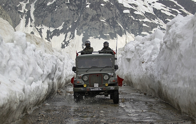 Indian Army soldiers travel in a vehicle on a mountainous road covered by snow after the Srinagar-Leh highway