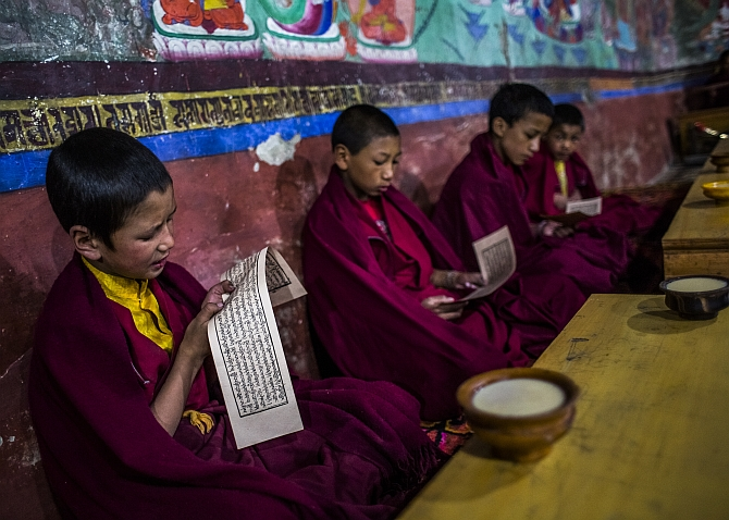 Young Buddhist monks pray during morning prayers at the Thikse Monastery near Leh
