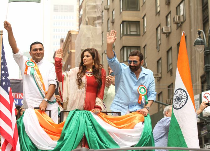 Actors Raveena Tandon and Sunny Deol wave to the crowds as they participate in the India Day parade.