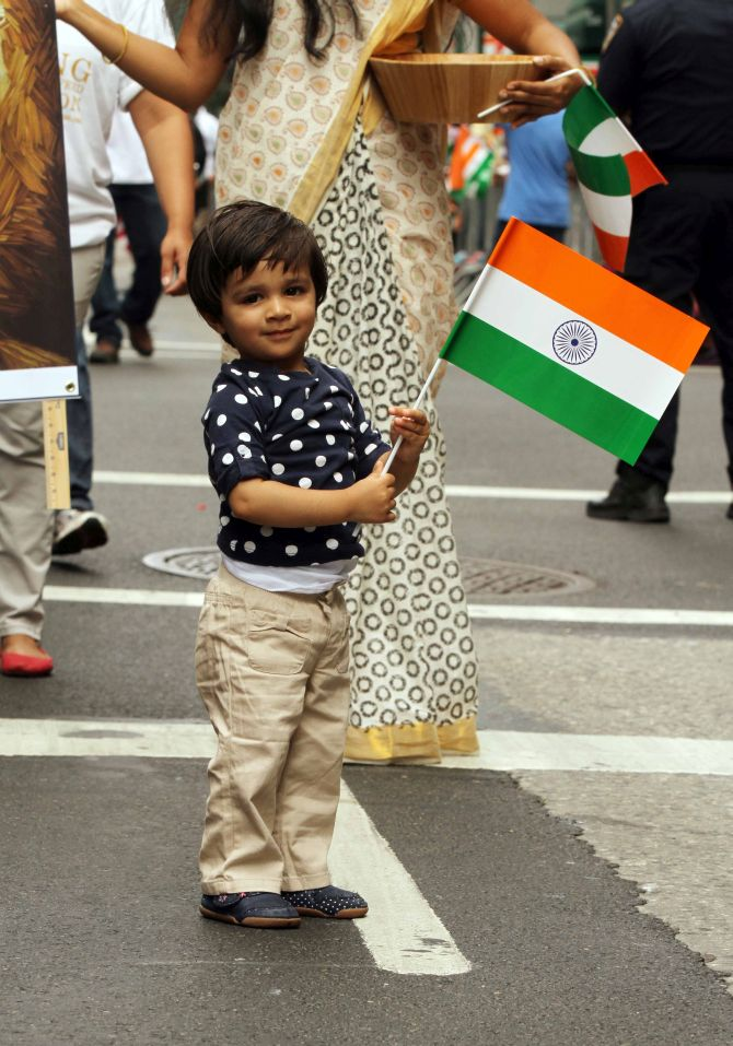 Little boy holds the Indian flag during the parade.