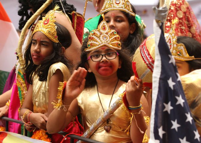 Some children on a flotilla dress up like Hindu gods Ram and Hanuman during the parade.