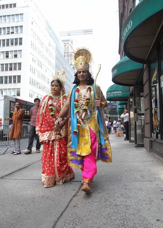 A couple dressed as Hindu gods walk down a street in New York, as they participate in the parade