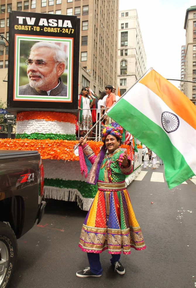 A man dressed in traditional Indian clothes waves the Indian flag as a flotilla with the picture of Indian Prime Minister Narendra Modi is behind him.