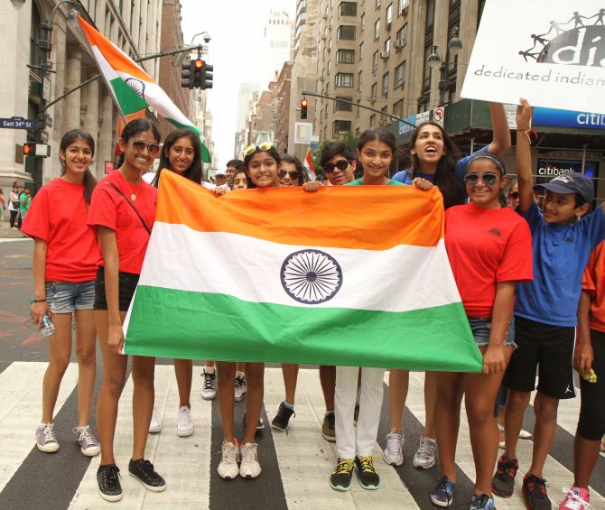 Girls are all smiles at they hold the Tricolour in their hand during the India Day parade.
