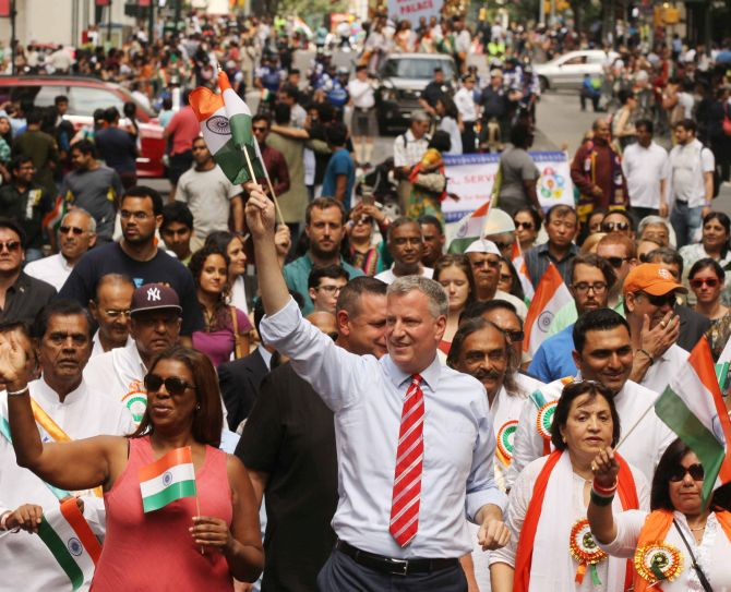 New York City Mayor Bill de Blasio, waves an Indian flag and walks among the public during the parade