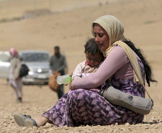 A displaced woman and child from the minority Yazidi sect, fleeing violence from forces loyal to the Islamic State in Sinjar town, rest as they make their way towards the Syrian border