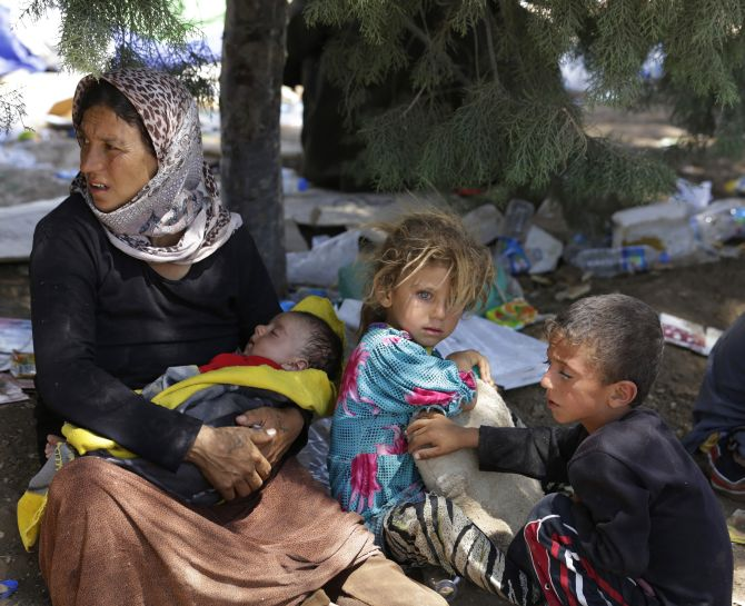 A displaced family from the minority Yazidi sect wait for food and water.