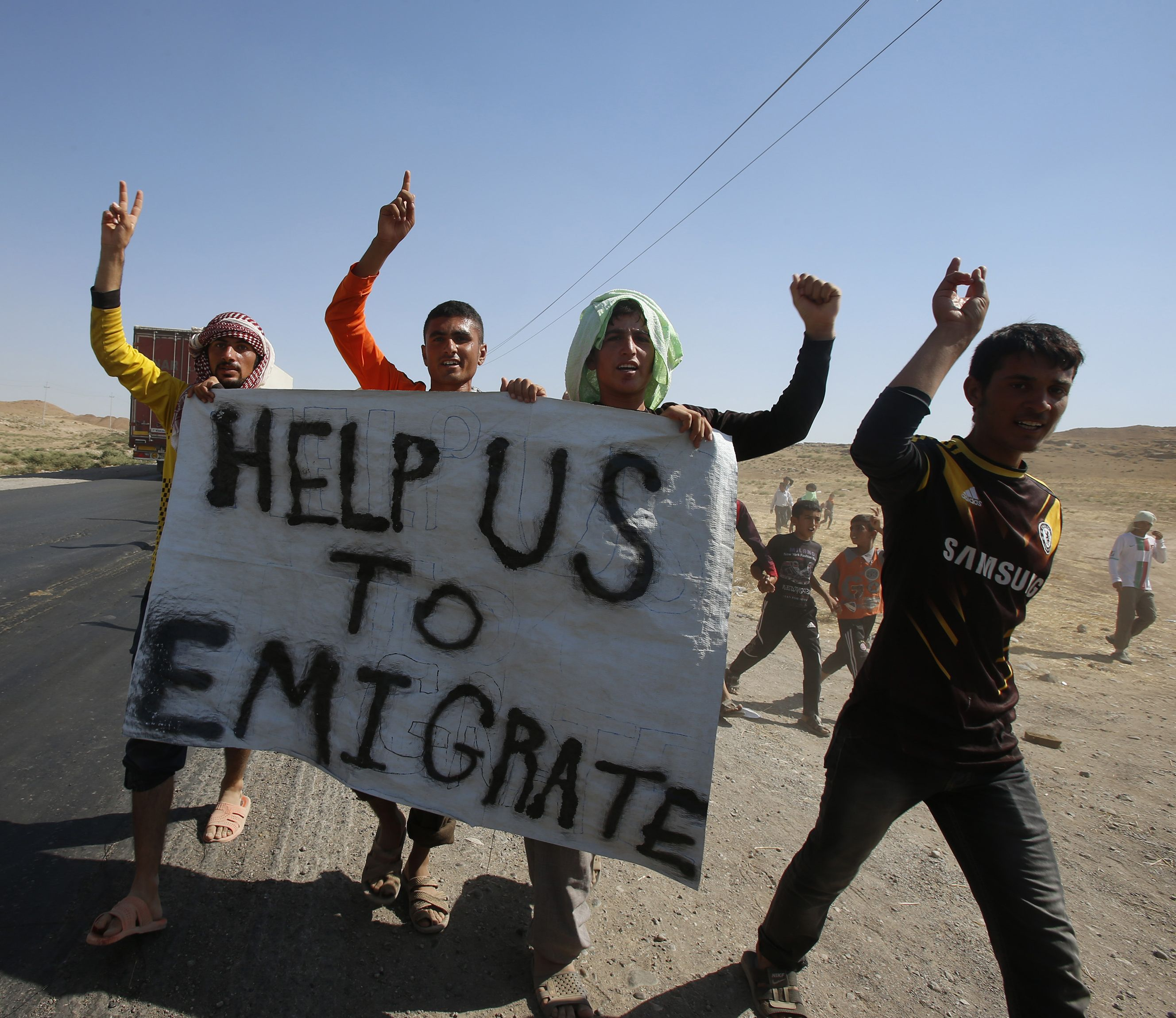 Displaced people from the minority Yazidi sect, who fled the violence in the Iraqi town of Sinjar, hold a banner as they take part in a demonstration at the Iraqi-Syrian border crossing in Fishkhabour, Dohuk province.