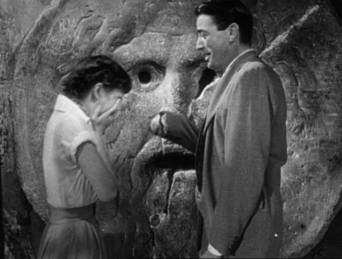 A scene from the 1953 movie Roman Holiday featuring Audrey Hepburn, Gregory Peck at the Mouth of Truth.