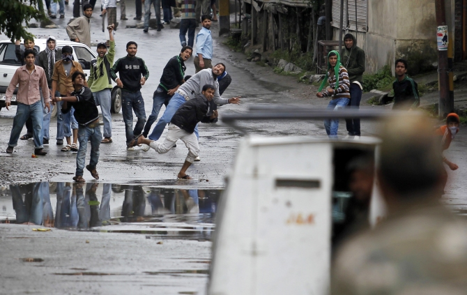 Kashmiri Muslim protesters throw stones and pieces of bricks at an Indian police vehicle after police stopped an anti-Israel protest organised by Geelani in Srinagar.