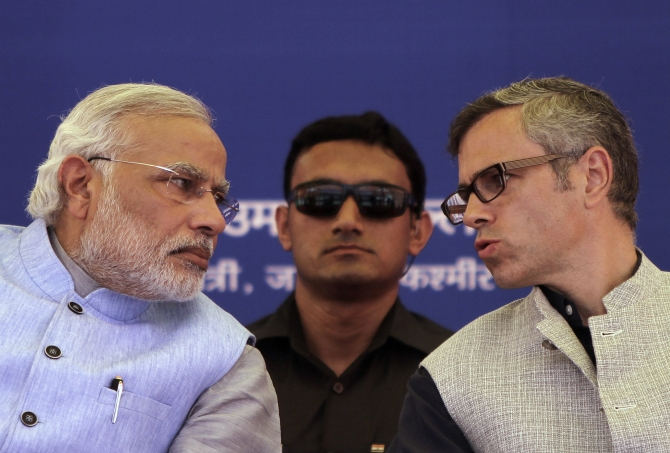 Kashmir's Chief Minister Omar Abdullah (right) speaks with Prime Minister Narendra Modi as a security personnel watches after the inauguration ceremony of a train on a new stretch of railway to the town of Katra, northwest of Jammu.