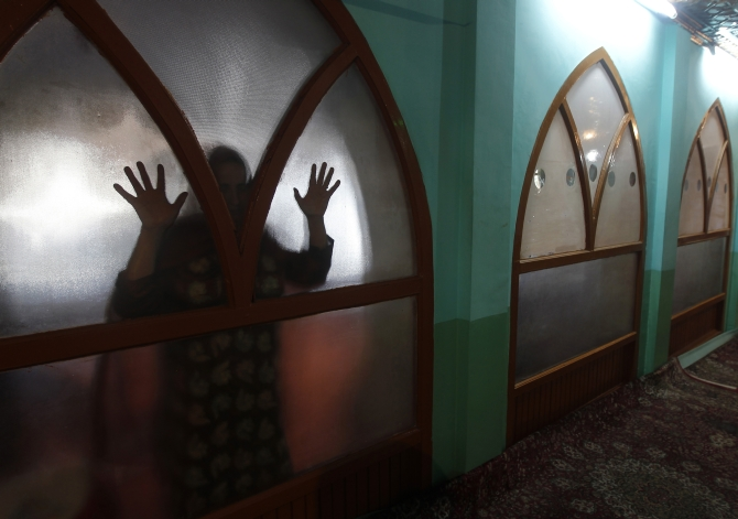 A Kashmiri Muslim woman prays behind a glass window, as women are not allowed to enter, at the shrine of Sufi saint Ziarat Sharief Hazrat Syed Yaqoob Sahib in Srinagar.