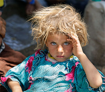 A Yazidi girl, fleeing the violence in the Iraqi town of Sinjar, at the Iraqi-Syrian border crossing.