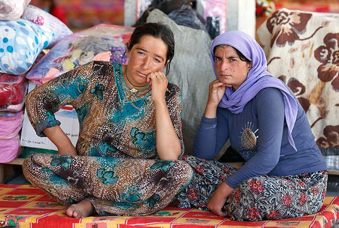 Women rest in an abandoned building being used with other displaced people as their main residence outside the city of Dohuk.