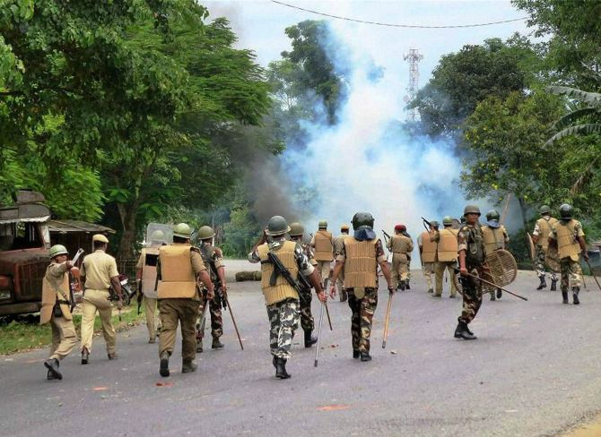 Police personnel disperse protestors blocking the National Highway in a protest