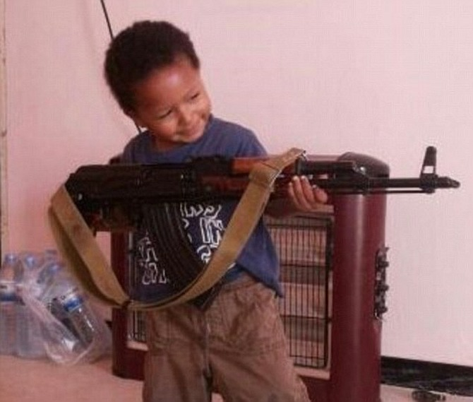 Dare's Twitter profile shows her toddler son posing with an AK47 rifle.