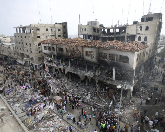 Palestinians gather around the remains of a commercial center, which witnesses said was hit by an Israeli air strike on Saturday, in Rafah in the southern Gaza Strip.
