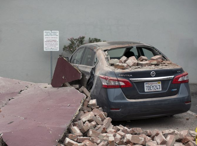 A car damaged by bricks falling during an earthquake is seen next to a downtown building in Napa, California