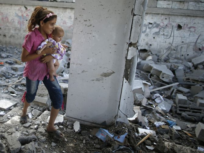 A Palestinian girl holding her sister walks through debris near remains of a mosque, which witnesses said was hit by an Israeli air strike