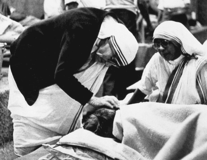 Mother Teresa attends to a patient in her home for the dying in Calcutta's teeming slum in this photograph taken on February 2, 1986, hours before the arrival of Pope John Paul.