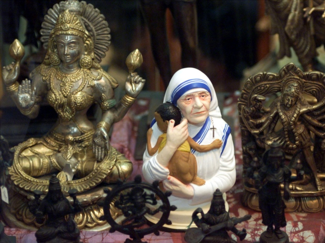 A statue of Mother Teresa holding a child is on sale along with idols of two Hindu goddesses in Kolkata.