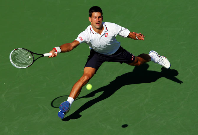 Novak Djokovic of Serbia returns a shot against Paul-Henri Mathieu of France during their US Open men's second round match on Thursday