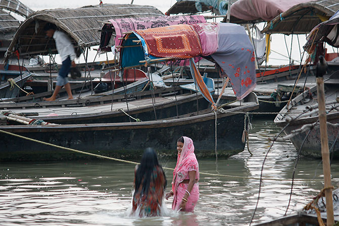 Women take a dip on the banks of the Sangam