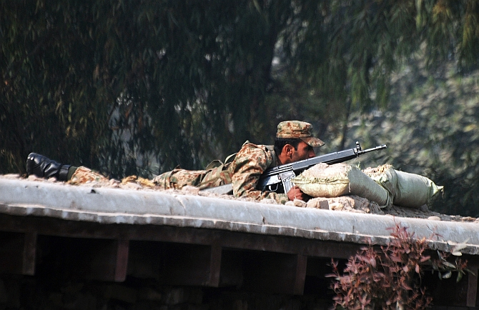 Image: A Pakistani soldier takes up a position above a road near the school. Photograph: Khuram Parvez/Reuters