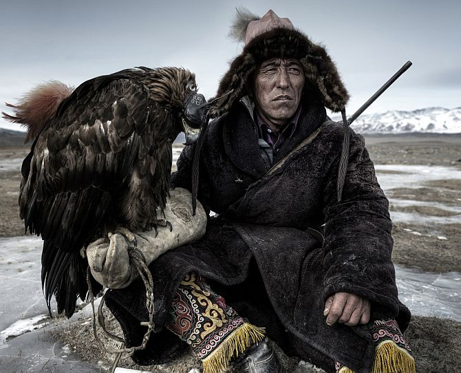 A hunter rests in his little house on the plains in western mongolia with his Eagle which is hooded and cat under the table!