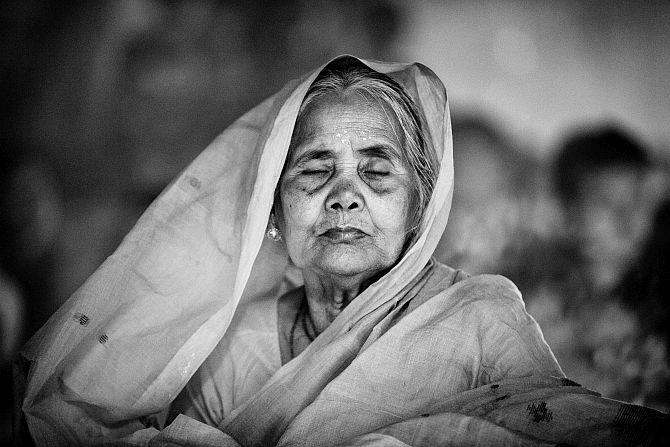 An old Hindu woman sits with lights (Prodip) and prays to God in front of Shri Shri Lokanath Brahmachar Ashram temple during the Rakher Upobash at Barodi, Narayangonj, near Dhaka, Bangladesh